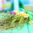 Stock Photo: Bouquet of wild flowers and herbs, on wooden table on bright background