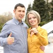 Portrait of happy beautiful couple with car key, standing near the car — Stock Photo
