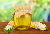 Jar of honey with flowers of acacia on wooden table, on bright background — Stock Photo