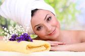 Mulher jovem e bonita com toalha na cabeça no fundo brilhante — Fotografia Stock