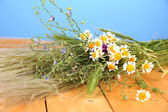 Bouquet of wild flowers and herbs, on wooden table on color background — Stock Photo