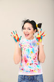 Young pretty painter with hands in paint, on gray background — Stock Photo