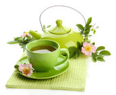 Cup and teapot of herbal tea with hip rose flowers, isolated on white — Stock Photo