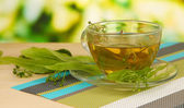 Glass cup of tea with linden on napkin on wooden table on natural background — Stock Photo