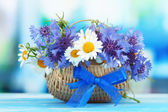 Beautiful bouquet of cornflowers and chamomiles in basket on blue background — Stock Photo