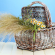Bouquet of wild flowers and herbs, in wicker basket, on color background - Stock Photo