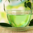 Transparent cup of green tea on bamboo mat, on nature background - Stock Photo