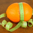 Orange with measuring tape, on wooden background - Stock Photo