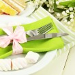 Table setting in white and green tones on color  wooden background - Stock Photo