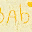 Word baby making with powdered milk on yellow background — Zdjęcie stockowe
