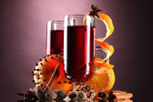 Mulled wine in the glasses, spice and orange on purple background — Stock Photo