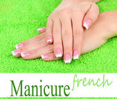 Woman hands with french manicure on green towel — Stock Photo