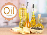 Different types of oil with sunflower seeds on table in kitchen — Stock Photo