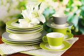 Tomma tallrikar och koppar på träbord på grön bakgrund — Stockfoto