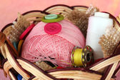 Variety of buttons and a ball of yarn in a basket on a pink background — Stock Photo