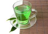 Transparent cup of green tea on bamboo mat, isolated on white — Stock Photo