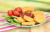 Fried chicken nuggets with vegetables and sauce on table in park — Stock Photo