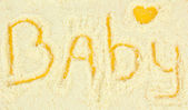 Word baby making with powdered milk on yellow background — Stock Photo