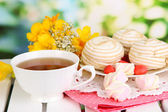 Beautiful composition with cup of tea and marshmallow on wooden picnic table on natural background — Stock Photo