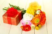 毛茛属 (波斯毛茛属植物) 和礼品,在白色的木制背景 — 图库照片