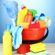 Cleaning items in bucket on  color background - Стоковая фотография