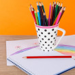 Colorful pencils in cup on table on orange background — ストック写真