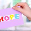 Hope word on piece paper in hand on window background - Stock Photo