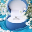 Flowers  and engagement ring on blue cloth - Stock Photo