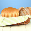 Bread in wicker basket, on wooden table, on color background - Stock Photo