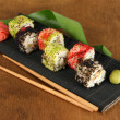Tasty Maki sushi - Roll on mat on brown background - Stock Photo
