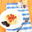 Spaghetti with tomatoes and basil leaves on napkin on wooden background — Stock Photo #25541861