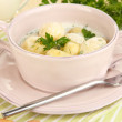 Tender young potatoes with sour cream and herbs in pan on wooden table close-up - Stock Photo