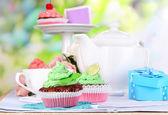 Mooie cupcakes op eettafel op natuurlijke achtergrond — Stockfoto