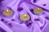 Candles on purple fabric close-up — Stock Photo
