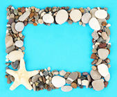 Frame of sea stones on color background — Stock Photo