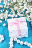 Flowers and gift on blue cloth — Stock Photo