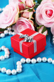 Rose and gift box on blue cloth — Stock Photo