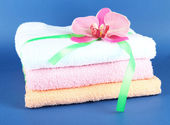 Towels tied with ribbon on blue background — Stok fotoğraf