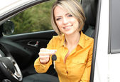 Portrait of happy beautiful woman with car key, sitting in the car — Stock Photo