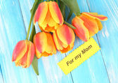 Beautiful orange tulips on color wooden background — Stock Photo