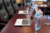 Empty conference room with laptops on table — Stock Photo