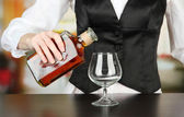 Barman hand with bottle of cognac pouring drink into glass, on bright background — Stock Photo