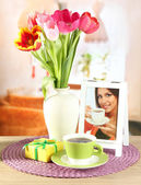Beautiful tulips in bucket with gifts and cup of tea on table in room — Stock Photo