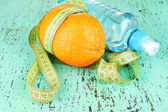 Orange with measuring tape, bottle of water, on color wooden background — Stock Photo