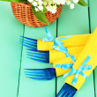 Blue plastic forks wrapped in yellow paper napkins, on color wooden background — Stock Photo