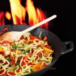 Noodles with vegetables on wok on fire background - Stock Photo