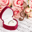Treble clef, roses and box holding wedding ring on musical background — Stock Photo #25673579