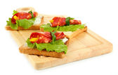 Salami rolls with paprika pieces inside, on roasted bread, on wooden board, isolated on white — Stock Photo