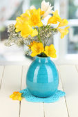 Beautiful bouquet of freesia in blue vase on wooden table on window background — Stock Photo