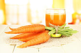Heap of carrots, glass of juice, on color wooden table on bright background — Stock Photo